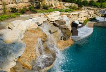 Pool Carved into Mountain / This inground massive swimming pool was made with natural boulders and carved into the side of a mountain slope. It has a double water feature, spa, sun deck and ample patio space.