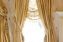 Window curtain / a piece of material suspended at the top to form a covering or screen, typically one of a pair at a window.