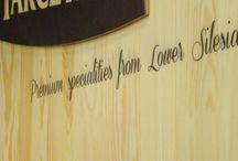 Regał produktowy z litego drewna / Regał dla firmy Tarczyński wykonany z litego drewna. Przygotowany na różne produkty: haki na produkty wiszące oraz półki do ułożenia innych materiałów. Do produkcji użyto drewna sosnowego, bezsęcznego. Stand posiada także elementy drukowane: toper z logotypem oraz elementy dekoracyjne. Wydruk wykonano bezpośrednio na materiale.