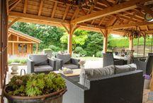 Engelse Cottage Tuin / Slingerende paadjes brengen je naar mooie,romantische plekken in de tuin,omgeven door vele bloemen en prachtige bomen. Vanuit de veranda met rieten dakbedekking heb je zicht over de hele ,natuurlijke tuin.  De tuineigenaren genieten van dit uitzicht tijdens alle jaargetijden,omdat de veranda o.a. voorzien is van een luxe buitenkeuken,heaters en een mooie gaskachel.  Deze tuin is aangelegd door: Hoveniersbedrijf Miggiels & van Amstel!