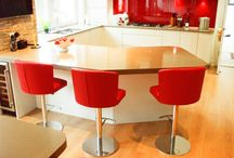 The Wow Factor / Sometimes a single object or a series of objects can make the kitchen really eye catching and different. Here are examples with the fish tank, incorporated into the breakfast bar, and the kitchen which has soft colours apart from the Red Barstools, Chairs and the Matching Splashback