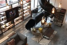 BOUTIQUES | STORES / DEUX BOUTIQUES -   « L'idée, c'est de faire oublier aux gens qu'ils magasinent. ».   La première boutique est dans un local du boulevard Pierre-Bertrand et contient un comptoir-bar où le service de slush et de café est offert gratuitement afin d'installer une ambiance conviviale et survoltée.  Le même concept a été repris dans la deuxième boutique à Place de la Cité faisant pignon sur rue.  Avec deux mezzanines aménagées en lofts et une immense glissade faisant le lien entre les deux niveaux, elle invite à y faire le détour pour découvrir son esprit funky et haut de gamme sortant de l'ordinaire.