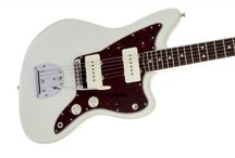 GAK Fender Jazzmasters / The Fender Jazzmaster is an electric guitar designed as a more expensive sibling to the Fender Stratocaster. First introduced at the 1958 NAMM Show, it was initially marketed to jazz guitarists, but found favor among surf rock guitarists in the early 1960s.