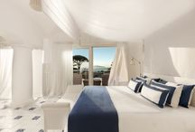 Capritouch Rooms & Suites / The newest Capritouch Suites, inspired by the homonymous brand Concept, hold the history, art, architecture and craftsmanship of Capri: panoramic terrace overlooking the sea, soft colors and Mediterranean lines, enriched by Loro Piana fabrics and fine linens and cottons. White and blue hand-painted ceramic floor, bedroom and living area separated by columns, arches and cross vaulted ceilings. Furniture custom made according to the most traditional artisan techniques.