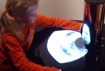 """Anamorfoses / An interactive exhibit in which children can play with a camera that projects a deformed image (in realtime) according to cylindrical deformation. This technique was used in the middle-ages to visually encode obscure paintings. When pressing the """"take picture"""" button, the image is saved and can be printed. Together with a small cylinder mirror this can be given away (or sold) as a souvenir."""