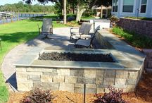 Waterside Patio Design / In this project, we used our hardscaping skills to create a patio that showcased exquisite stone work throughout, from the custom fire pit to the large outdoor kitchen with ample space for grilling, food preparation, and service. The size was just right for the size of the lot (and offered just the right amount of seating) and we ensured that the patio was complete with a landscaping design to match its new found elegance, utility, and style. It begs to be enjoyed.