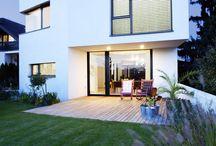 Dom s dvojitým výhľadom / Osadením domu ďalej od ulice vznikol vpredu priestor na malú záhradku s výhľadom na mesto. Týmto sa podarilo vytvoriť jeden súvislý priestor, ktorý sa ťahá od prednej záhrady až do zadnej záhrady. Vďaka preskleným stenám na oboch stranách domu je celý priestor vizuálne prepojený a zeleň sa tak stáva súčasťou interiéru.