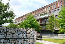 BETAFENCE: Gabiony na Osiedlu Bażantów / Część ogrodzenia osiedla mieszkaniowego w Katowicach wykonano z koszy gabionowych. Gabiony z siatki zgrzewanej w postaci murków i ścian wypełniono różnokolorowym piaskowcem.