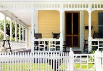 in a yellow house with a picket fence