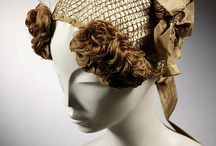 Ladies' Hair- 1820's / The important transition from the simple, doll-like coiffures of the Regency era into the towering topknots of the 1830's. Characterized by center parts, neat, stiff curls framing the face, volume and depth, knot or coil on the top of the head