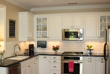 Subway tile, ceiling lights, hardwood floors, dark countertop, light cabinets, large double sink.