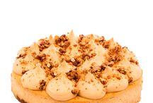 Banana-caramel cheesecake / Korpus z Lotus sušenek a oříšků, který doplňuje nadýchaný krém z Philadelphie, banánů a domácího karamelu. Povrch dortu zdobí pucky z mascarpone s karamelem, které jsou posypány oříškovým krokantem.