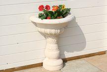 Vasques de jardin en pierre reconstituée / Alentour vous propose des vasques de jardin en pierre reconstituée de différents styles et dimensions: une vasque moulurée à fixer au mur; une vasque sur pieds épais à ouverture hexagonale; deux vasques à ouverture ovale sur pieds-socle (petit et grand modèle). Nos vasques ont une finition lisse ou une surface imitant la pierre taillée artisanalement. Ils vous serviront de récipients décoratifs aux lignes douces pour planter vos fleurs ou vos herbes aromatiques.