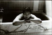 Photographes_Junku Nishimura / Mélancolie et nostalgie  tirages noir et blanc emplis d'âme imparfaits, un peu flous, impressionnistes. Ce dispositif esthétique est aussi un outil critique de la modernité, de l'ordre établi, du progrès et de la culture contemporaine. Au fil des portraits qui constituent cette série – réalisés, pour beaucoup d'entre eux, de nuit, dans des bars – il est question d'amis et d'inconnus entonnant ensemble l'hymne disparu à un pays fier, et des murmures d'un peuple, d'une famille, ou d'un homme seul.