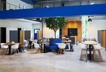 Conec Cafeteria und Konferenz Lippstadt / Die Cafeteria wurde als Raum in Raum-Konzept umgesetzt. Für ein offenes Raumgefühl wurde auf seitliche Sichtschutzelemente gesetzt, die versetzt positioniert sind.  Ein Rahmen in tiefem Blau nimmt die Farben des Corporate Designs des Unternehmens auf und steckt den Eingangsbereich symbolisch ab. Das Interiorkonzept wurde clean und reduziert gestaltet, wirkt aber durch den Einsatz unterschiedlicher Materialien und Farben lebendig und einladend.