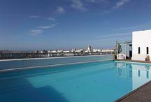 La terrasse et la piscine de l'Heure Bleue / Avec une vue imprenable sur l'océan et la Médina, vous apprécierez la terrasse panoramique et sa piscine chauffée. Sur fond d'azur, l'eau turquoise du bassin vous fait la promesse d'un bain de fraîcheur, les chaises longues du solarium appellent au farniente et le bar promet de ne pas laisser vos envies sans réponse.