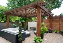 Alair Homes Richmond Hill - Modern Pergola Outdoor Living / Alair Homes | Pergola | Renovation | 200 sqft | This modern deck includes a solid wood pergola, privacy screen, sleek tiled outdoor fireplace, glass railings, in-step lighting, and minimalist landscaping.
