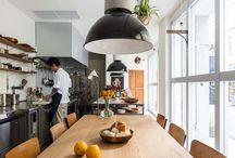 """FOOD WORKER FUNAKI (Shop) / [シンプルなキッチンとクラフトで食の楽しさを演出する]「""""What is tasty?""""=美味しさとは?」をコンセプトにしたアトリエキッチン。料理のケータリングやスタジオ・キッチンのレンタルなどを通じて、食の新しい形を提案している。通常は各種ワークショップ、ポップアップストア、料理教室、撮影スタジオなどとして利用されている。  食を通じて生まれる会話や感覚を共有することを大切にしたい、というのがオーナーシェフの意向だった。そこでダイニングテーブルの周りを厨房が取り囲むようなレイアウトを採用。キッチンとダイニングの距離が近く、友人の家に遊びにきたような感覚が味わえる。「シンプルで温かみのある空間を」というシェフのリクエストにも配慮し、白で統一されたインテリアに木目が美しい木材を組み合わせた。ガラス張りのファサードから外光がたっぷりと入り、開放感のある空間となっている。"""