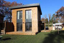 Maison SO / Trois maisons R+1 de 89m² et 300m² de jardin, destinées à un usage locatif dans une copropriété.  Grand salon avec cuisine à l'américaine au rez-de-chaussée. L'étage comprend trois chambres et une salle de bain. Ces maisons possèdent des poêles à granules pour office de chauffage. Les toitures plates sont réalisées avec une étanchéité EPDM (membrane d'étanchéité).