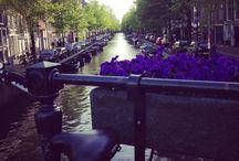 """Amsterdam / Amsterdã é simplesmente uma cidade apaixonante! Além do cenário cinematográfico, com seus canais e suas charmosas casas-barco, a cidade está repleta de atrações interessantes para todos os gostos. Como se isso não bastasse, a """"capital mundial da bicicleta"""" tem um povo super acolhedor, o que torna a cidade ainda mais encantadora."""