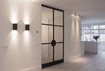 Amstelveen: taatsdeuren Osiris Hertman / In Amstelveen plaatsten wij deze prachtige taatsdeuren. De deuren zijn gemaakt van DRM-P10 profielen en zijn gepoedercoat met RAL 9005 fijnstructuur. Deze taatsdeuren zijn ontworpen in samenwerking met designer Osiris Hertman. Hertman ontwierp bijzondere en unieke ronde handgrepen voor een set stalen deuren. Wij hebben dit ontwerp gerealiseerd.