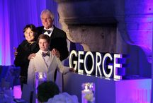 George's Super Fun Bar Mitzvah Night at L'Escale in Connecticut / Our Bar Mitzvah boy, George, is a young wanderlust who has traveled extensively around the world and he also loves colorful neon lights. So we created his Bar Mitzvah theme to reflect his fun nature and the love of traveling. From the entrance we erected 8 x 14 feet world map escort card wall with living plants and hanging mini planes all over the World map. Inside the party, George's colorful glowing neon light murals and the whole party design made the night super awesome