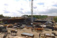 Budowa wiaduktu MS-22 w ciągu S7 metodą nasuwania podłużnego / Stanowisko prefabrykacji dźwigara obiektu MS-22 zostało zaprojektowane w sposób nietypowy. W pierwszej kolejności wykonane zostały trzy rzędy ław fundamentowych. Cały ciężar rusztu stalowego z szalunkiem oraz betonowanych segmentów przenoszony jest za pomocą żelbetowych belek nośnych o geometrii 0,8 x 1,4 x 27,4 m. Każda z nich podparta została w trzech punktach (na przecięciu z ławami fundamentowymi) przy pomocy siłowników hydraulicznych o skoku 300 mm.