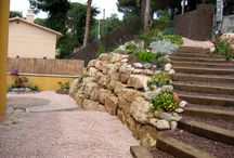Rocalla en Cataluña / Rocalla conteniendo un talud.Plantaciones de vegetación autoctona y/o bien adaptadas,  riego por goteo diferenciado en cada plantación. Una  escalera de traviesas comunica la entrada con la  zona de estar , un  patio de adoquines inmerso en grava rodeado por un jardín sostenible.