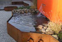 Booiman Tuinen BV. :Renovatie/ nieuwe tuinaanleg: project te Groningen / Foto impressie achtertuin. Tuinontwerp door K. Klap tuinarchitectuur. Bestrating van 100x100 oudhollandse tegels grijs met halfverharding van kwartsgrind (leverancier Zwaagstra te Hoogeveen). Vlonder en verhoogde zitbanken van Ipe Lapacho(leverancier Awood te Uden). Watermuur met verlichting (leverancier Kerstkoopmandesign te Ijlst). Beplanting en meerstammige bomen (leverancier Olaf Nijenkamp te Raalte).
