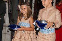 Cortejo de arras / Vestido en lino jengibre con tres volantes y adornos cachemir en tonos azules y blanco para las niñas. Los niños visten camisa, con canesú de alforzas y pantalón, siendo  de la misma tela y color que el de las niñas.