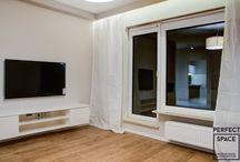 """Aranżacje Perfect Space - Jedno-dwuosobowe gniazdko / Utrzymane w ciepłej kolorystyce (brązy, beże, trochę szarości) mieszkanie będące startem w dorosłość dla młodej, przesympatycznej osoby. Oddzielna kuchnia z brązowymi frontami Zebrano Classic, skomponowana z białymi szafkami Mirror Gloss White wraz ze sprzętem AGD Whirlpoola sprawia wrażenie stworzonej do """"posiadówek""""."""