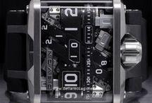 Devon Works / Il Tread 1 è un orologio con un meccanismo ibrido con pila al litio, composto da quattro minuscoli motori che muovono le cinghie sulle quali sono segnate le funzioni  di ore, minuti, secondi, e riserva di carica (solo a riposo), quest'orologio si ricarica per induzione, ed ha un'autonomia di due settimane.  La corona funge da switch on/off permettendo di regolare l'ora e i minuti...