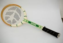 Mars of Kumanovo / Resined, wooden racket with green wording on white base. Its frame is decorated with lines in the direction of radius. The end of the grip is covered by a leather-like bandage, the strings has got a motif of an arrow. The material of the equipment is flexible and strong. The frame keeps the strings tight continuously. It is made for adults.