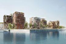 """RAVN_Fjordhusene / Bebyggelsen tegner sig som en """"søjleskov"""", der åbner op for overraskende kig til domicilet, fjorden, byen, Nørreskoven og havnen.  Fuldt udbygget vil bebyggelsen bestå af 12 kvadratiske boligtårne, alle med et fodaftryk på 16 x 16m.  En rektangulær facadestruktur tegner tårnenes overordnede arkitektoniske udtryk og brugen af tegl i dæmpede farver, varierende forbandter og detaljer tilfører hvert boligtårn sit eget udtryk."""