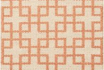 Orange & Grey / Orange accents add a burst of color to grey hues. An orange area rug makes a solitary statement, and immediately anchors a neutral-toned room and draws the eye.