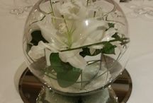 Flower arrangement / Centre table arrangement of lilies in a mirror cube in a glass bowl.