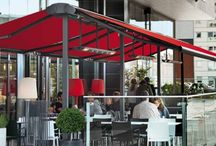 Butterfly Awnings / A 'Butterfly Awning' is a generic term referring to a free standing weather protection system with at least 2 retractable awnings either side of a sturdy goal post framework and there are many variations on this theme especially when your requirement is for commercial use, which the majority are used for.