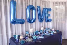 Blue, Navy + Silver Wedding Candy Bar / Set on gorgeous matte navy sequin linen, this wedding candy bar had great attention to detail. With our styling team playing on varied hues of a blue colour palette while blending silver and white accents throughout. Blue 'Love' Balloons captured the essence of our couple, whilst our in-house Graphics team produced some beautiful watercolour candy bar accents and chocolate wraps to tie together this bold statement sweets table.Youtube:https://www.youtube.com/watch?v=-ibQXqVmdoc&feature=youtu.be