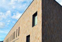 Centro sportivo-culturale Sanbàpolis / Parete ventilata a listelli verticali in piano naturale di porfido con trama sottile.