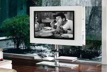 Televizní stolky a skříňky / TV skříňky mají více variant provedení. Nabízí se klasické uzavíratelné skříňky, které televizor zcela skryjí, aby na sebe zbytečně nestrhával pozornost rodiny. TV stolky ale ve velké většině případů slouží jako podstavec pro televizi, která je tak trvale vystavena zrakům členů domácnosti i návštěv.