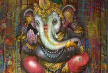 """GANESHA / O deus da boa fortuna Ganesha é o mestre do intelecto e da sabedoria. Representado como uma divindade amarela ou vermelha, com uma grande barriga, quatro braços e a cabeça de elefante com uma única presa, montado em um rato. É, habitualmente, representado sentado, com uma perna levantada e curvada por cima da outra.  Ganesha é o símbolo das soluções lógicas. Seu corpo é humano enquanto que a cabeça é de um elefante; ao mesmo tempo, seu transporte é um rato.  é o """"Destruidor de Obstáculos""""."""
