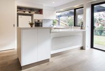 Greensborough - Modern Kitchen / Designer: Daniel Stelzer - Location: Greensborough This kitchen was previously very run down, impractical and borderline unsafe. Our clever Designer, Daniel, came in and fashioned a whole new space for our clients and their 70s built home. With a new product fresh in his mind, Daniel used Polytec's Legato laminate range to create a smooth, matt look that is elegantly touchable. The feature shelves above the fridge allow for display storage and visual interest.