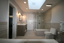 Monumental in Massapequa / A spacious master bathroom now updated features matching floor and wall tile, plus a generous amount of natural light without the use of a window.  Appointments include  large glass shower enclosure and a luxurious soaking tub situated with an open concept theme.