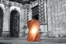 Pillar | Bench / 'Pillar' arises, mirroring the soul of Porto. A singular piece, with slender lines and finishes in copper leaf and high gloss varnish, it presents a duality of functions: it can be assumed as a table or a bench, according to the situation. The columns of the Order of St. Francisco, in the historical center of Porto, were the inspiration. 'Pillar', made with gold or silver leaf, demonstrates a city with a powerful and grandiose history.