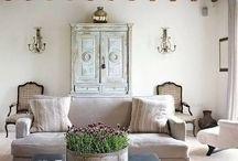 salon w stylu prowansalskim / Sprowadź Prowansję do swojego salonu i postaw na ściany w jasnych pastelowych odcieniach oraz meble z naturalnych materiałów. Pomieszczenie stanie się jeszcze bardziej przytulne; dzięki dodatkom w postaci miękkich poduszek, wełnianych koców i roślinności, która zazieleni twoje gniazdko!