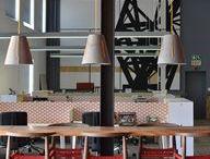 Nandos Office / Pomysł na aranżację kompleksu Nandos w RPA  wyszedł od afrykańskiej kuratorki i projektantki Tracy Lee Lynch, która zaprosiła do współpracy blisko 50 południowoafrykańskich designerów. Mieli oni zaprojektować i wykonać elementy wyposażenia wnętrz, nawiązujące do haseł przewodnich firmy, którymi są: duma, pasja, odwaga, uczciwość i rodzina. Wszystkie elementy są wykonywane ręcznie, z lokalnych materiałów – oddają w 100% afrykańską estetykę, podejście do funkcjonalności.