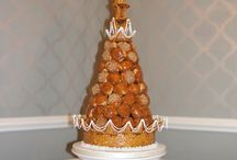 Traditional French Croquembouche / Something a bit different, a croquembouche is a traditional French wedding cake! Stacked high with profiteroles filled with Crème patissiére, flavoured with either orange liquor or vanilla bean syrup. Each profiterole is dipped in caramel and assembled on an almond, caramel nougatine base and decorated with nougatine shapes and finished with piped royal icing droplines.