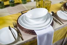 """Sunflower Cafe / Dinnerware: RATTAN CHARGER 12.5"""" ELLIPSE  PLATE  Flatware: LOFT - YELLOW GOLD   Glassware Collections: TUSCAN TUMBLER AMBER  Linen Athena 22"""" Napkins - White  Salt & Pepper Shakers: CYLINDER WHITE CHINA SALT & PEPPER  Seating: WALNUT CHIAVARI CHAIR  Votives: FROSTED SQUARE VOTIVE"""