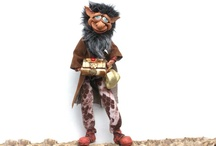 Leprecauni / Il Leprecauno è conosciuto con molti nomi in Irlanda e anche del suo aspetto fisico esistono varie versioni. Può indossare un panciotto, una giacca o un grembiule di cuoio, simbolo della sua professione. Le leggende più antiche lo vogliono infatti ciabattino delle Fate e, nonostante sia considerato un formidabile artigiano, si dice che produca solo scarpe sinistre.