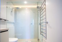 Grand frameless shower screens in bathroom / A double shower for him and her is elegantly concealed by the frameless shower screens. All our shower screens are Australian made and adhere to frameless glass standards in Australia.